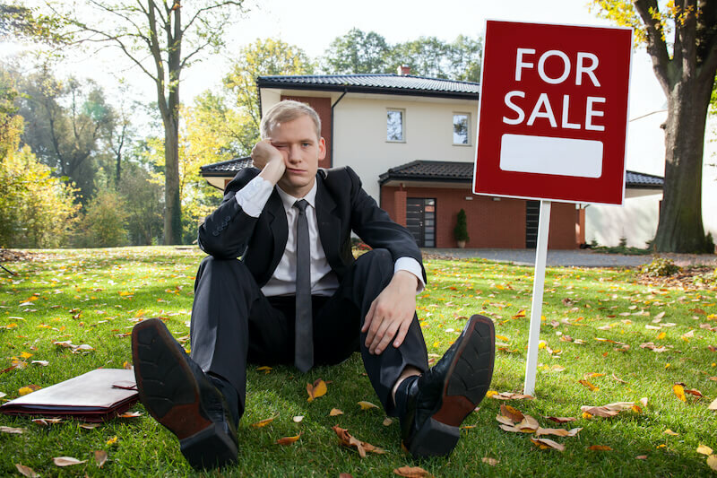 problematic guy beside a for sale sign with a distressed house in the background
