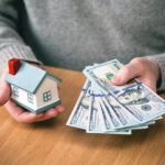local home buyers hands holding new hundred-dollar bills and toy house