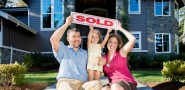 Family holding a sold sign after selling to Sell my house fast Salt Lake City home buying company.