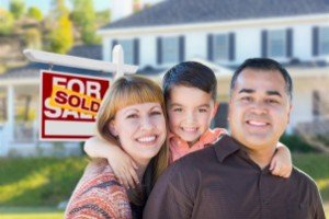 Sell my house fast Riverside | Young Family in Front of Sold Real Estate Sign House