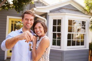 Punctuality Couple with keys standing outside new home sell my Riverside house fast