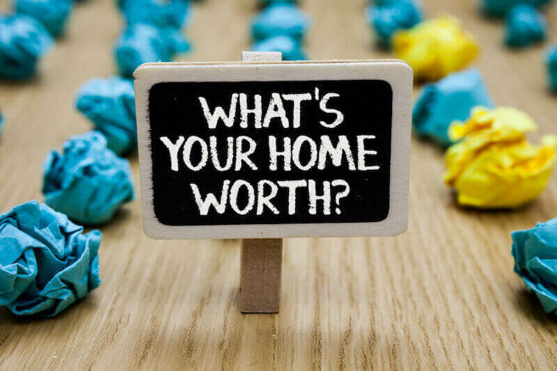 sign on table whats your home worth with crumpled papers