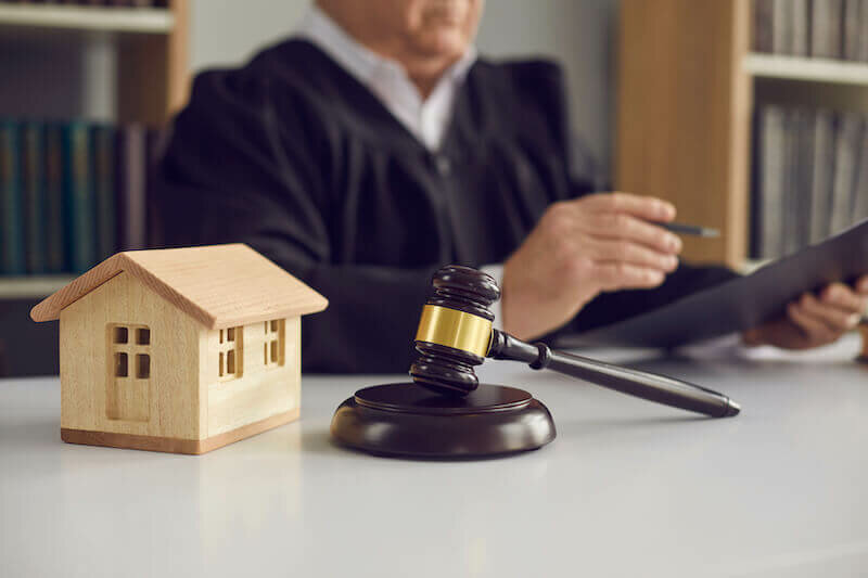 model house and gavel with a judge in the background reviewing Rhode Island Property Laws