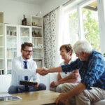 couple talking to a representative of a house buying company in Rhode Island