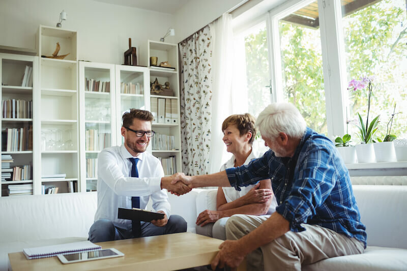 couple talking to a representative of a house buying company