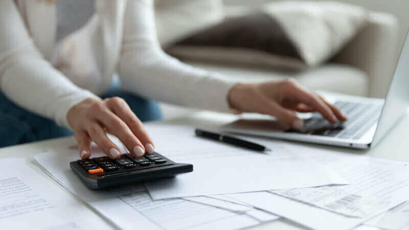 woman paying bills online - average cost of living in Maine