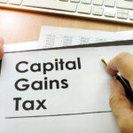 Male Hands holding documents with title capital gains tax