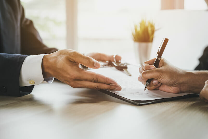 Man signing a contract to sell by himself without a realtor