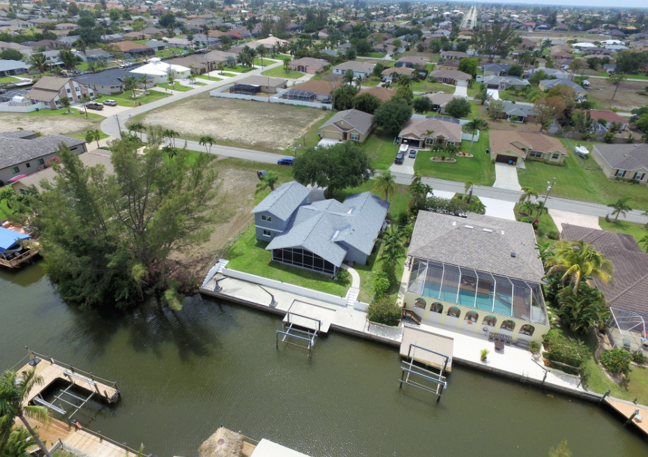 Drone image of fort myers foreclosure sale above the house and showing a canal and some trees and the horizon and showing local amenities and schools and the street and things that are important to a real estate foreclosure sale buyer that is looking for real estate deals and to sign up for real estate deal information