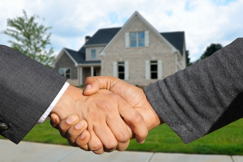 A handshake indicating that a house has been sold