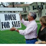 Couples putting up house for sale signage