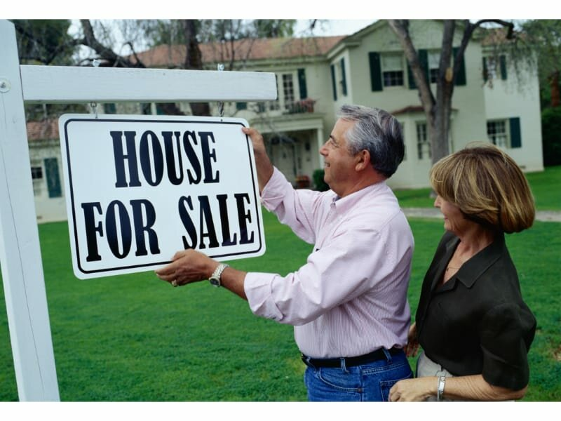 couple putting up for sale sign