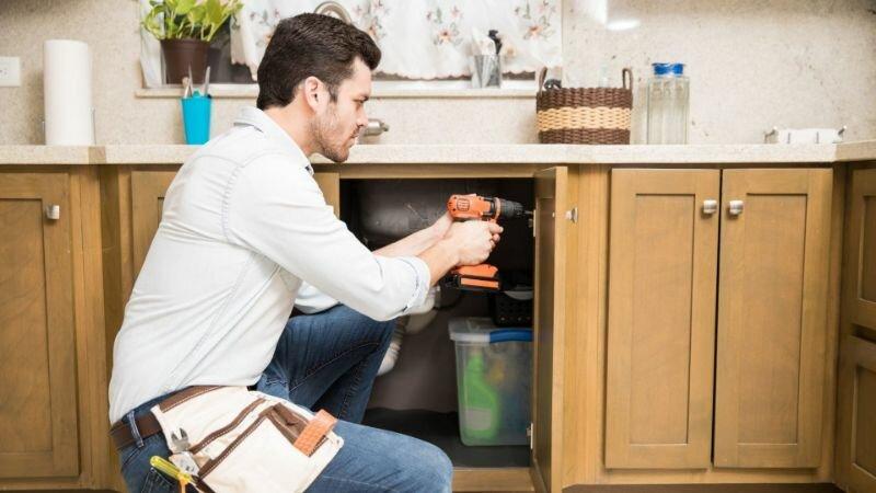 Handy man repairing cabinet