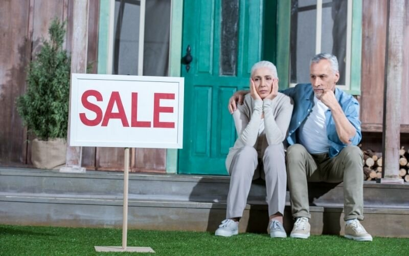 upset senior couple sitting on porch and selling their house