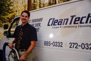 Mark Boek wearing a Winnie-the-Pooh tie holding a carpet cleaning wand standing in front of his carpet cleaning van that says Clean Tech Carpet & Upholstery Cleaning