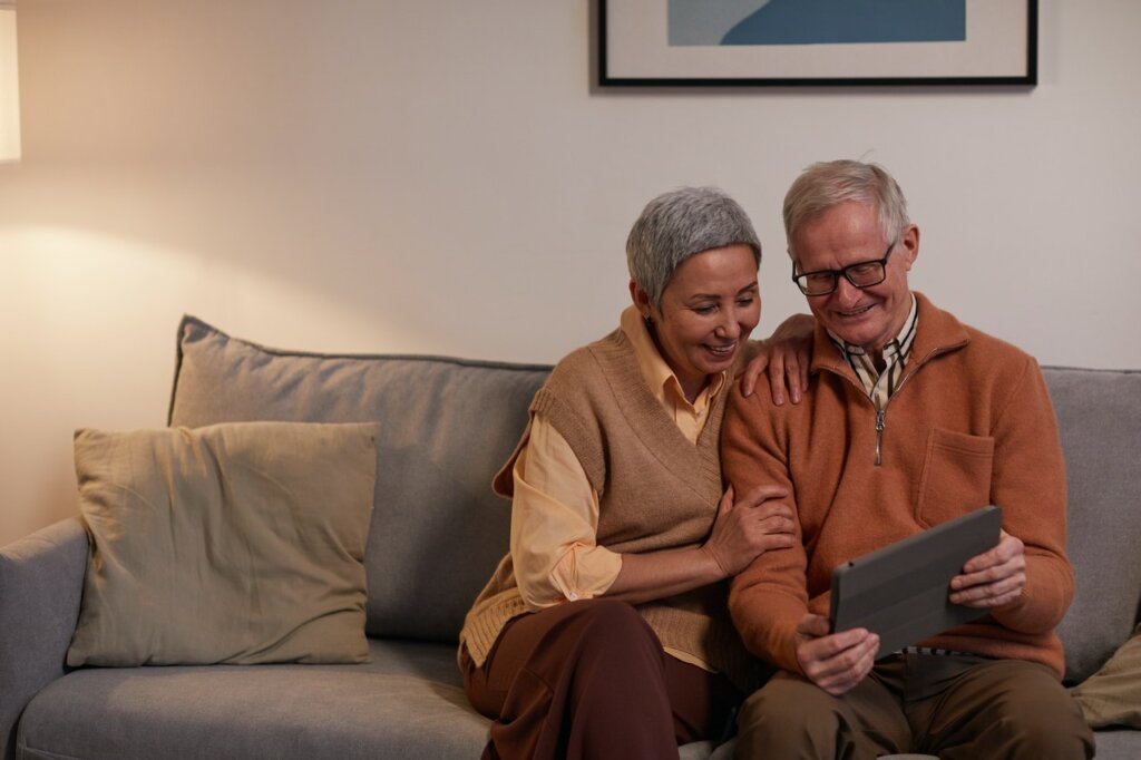 Two older adults looking at a tablet, thinking about the biggest reasons to downsize your home as a senior in Spartanburg