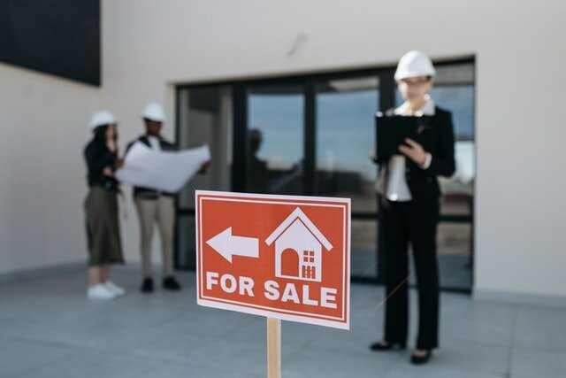 Three people standing in front of a property and next to a for sale sign