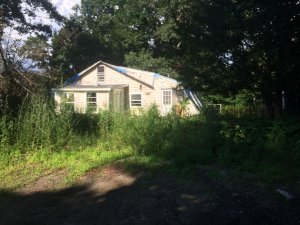 Need to sell your house fast? Yellow dilapidated and overgrown house in Massachusetts