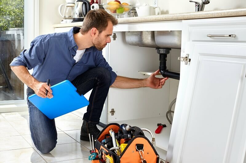 Man looking under the sink for foundation issues