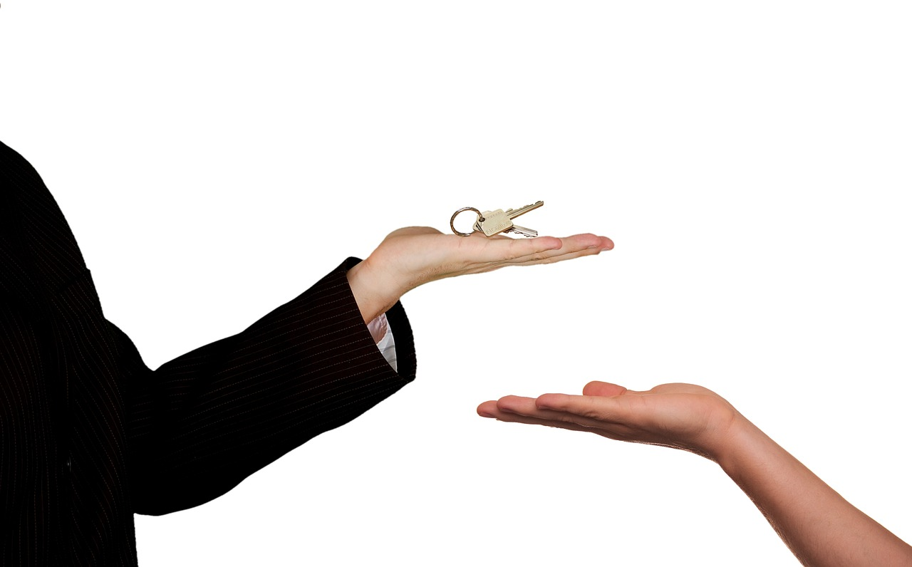 901 Investments Image of Real Estate Agent Handing Keys to Someone Selling A House