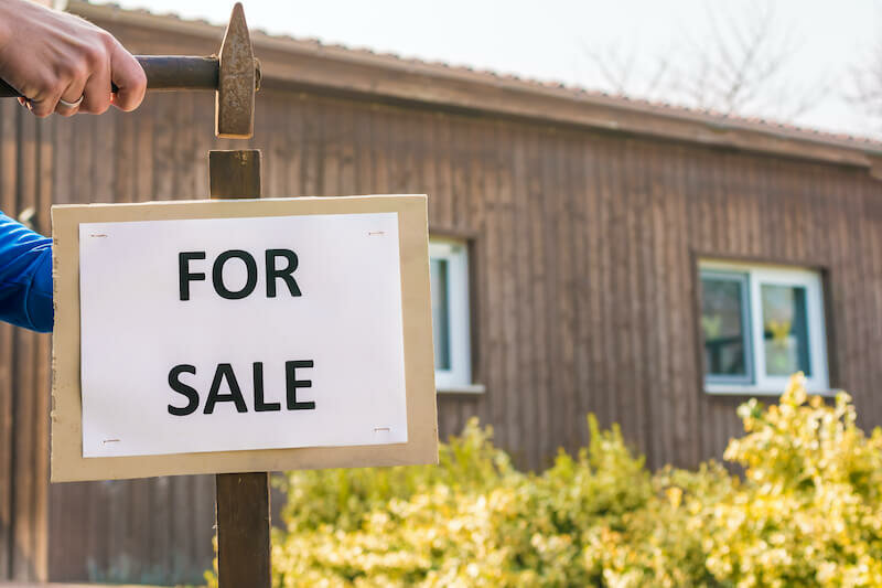 for sale sign hammered with a house in the background