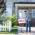 Young man with sale board selling a house with tenants in Kansas City