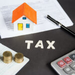 Tax words written on table with calculator,pen, miniature house with money and tax papers