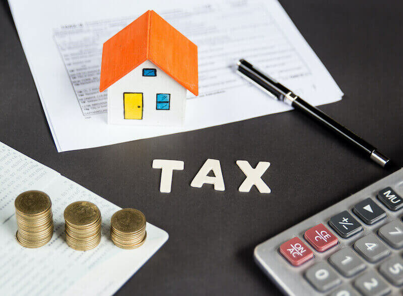 Tax words written on table with calculator,pen, miniature house with money and tax papers.
