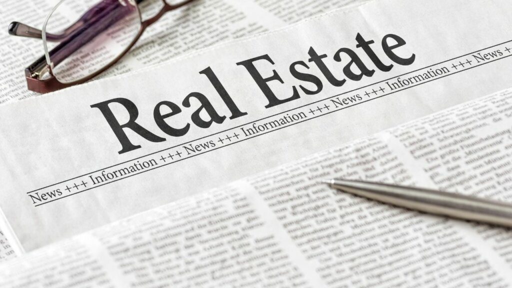 News Paper with words Real Estate as heading, a pen and glasses sitting on the paper.