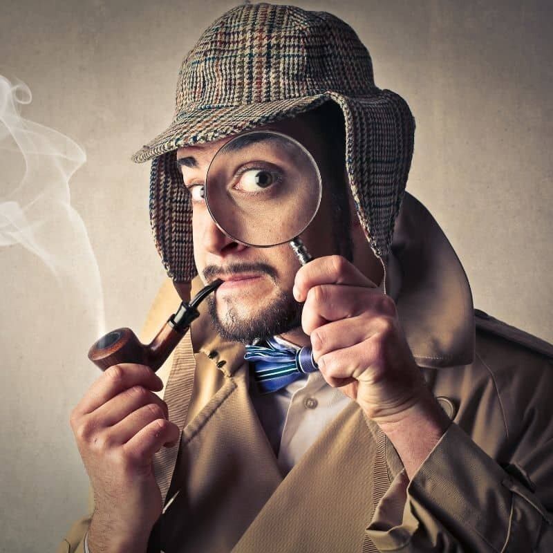 a man smoking a pipe with a magnigying glass up to his eye