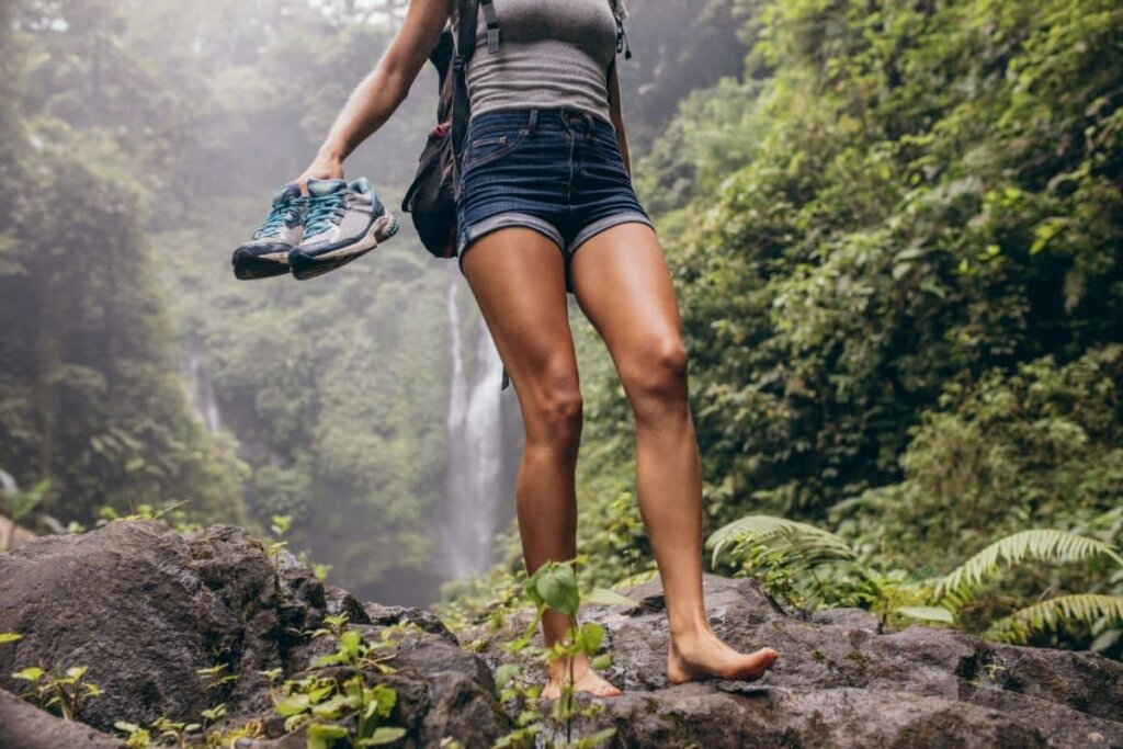 A girl hiking in the woods.  Waterfall in the background, she is baregoot and holding her sneakers.