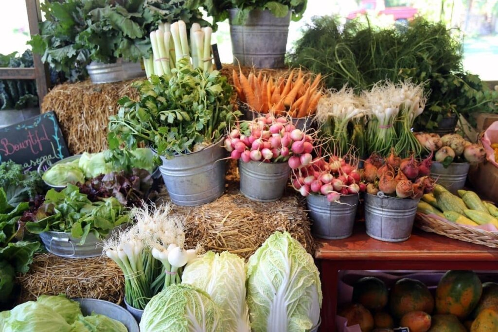 Fresh vegetables being displayed on a wood table and bails of hay at a farmer's market.