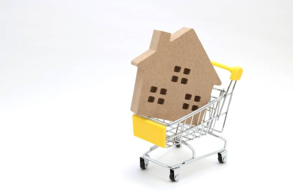 A little wooden house in a shopping cart.  Want to buy a house?
