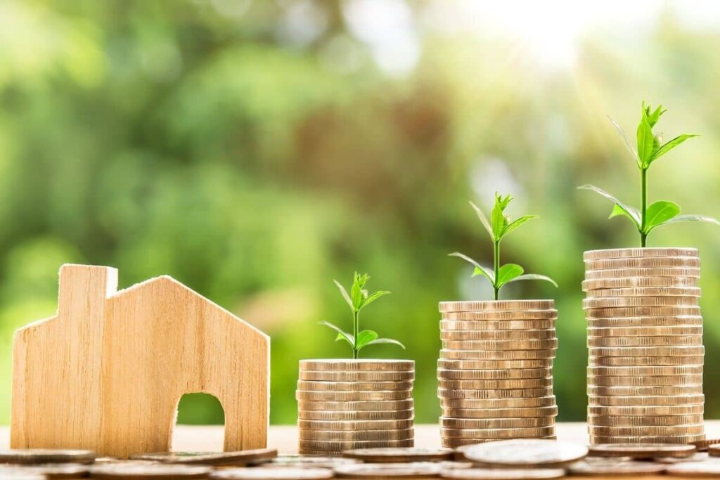 little wooden house next to several stacks of quarters with a fresh spring sprout growing from the top, green foilage background.  Housing prices are growing.