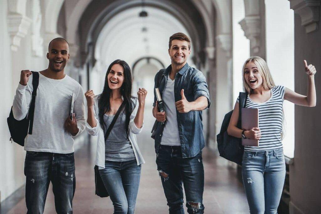 Four happy students walking down a long university hallway.
