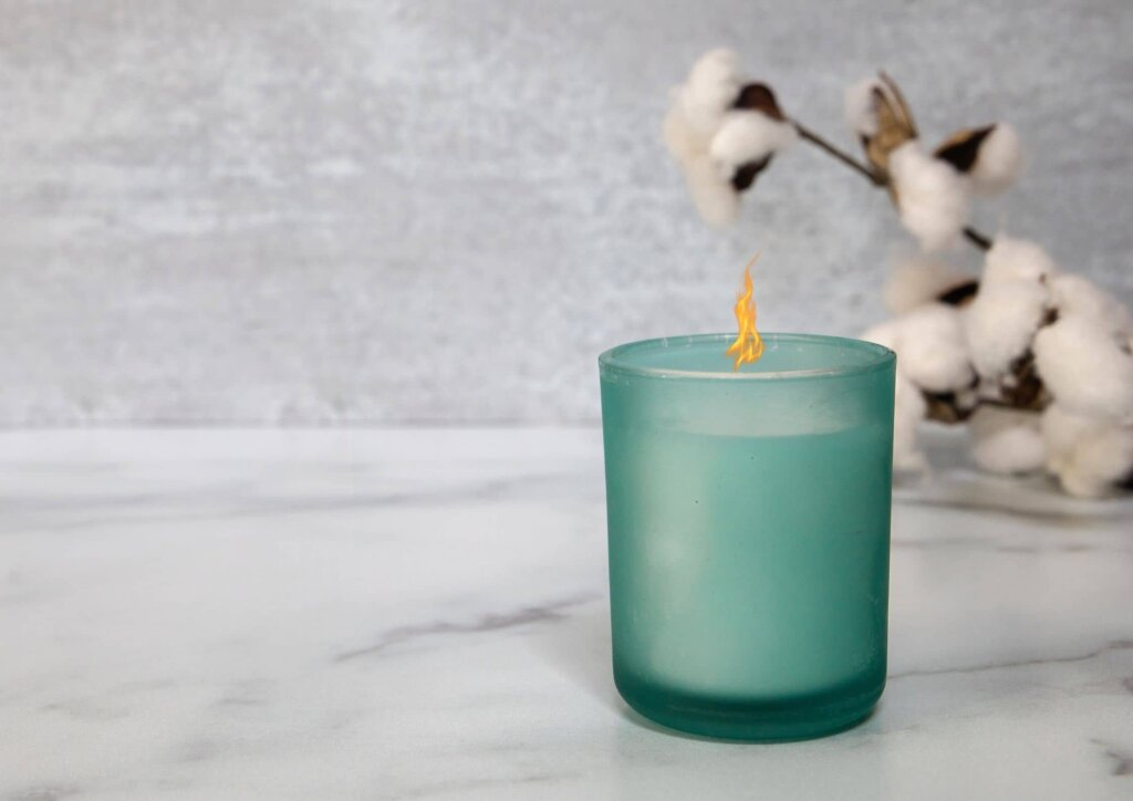 a candle in a blue jar on a marble counter top next to a cotton seed branch