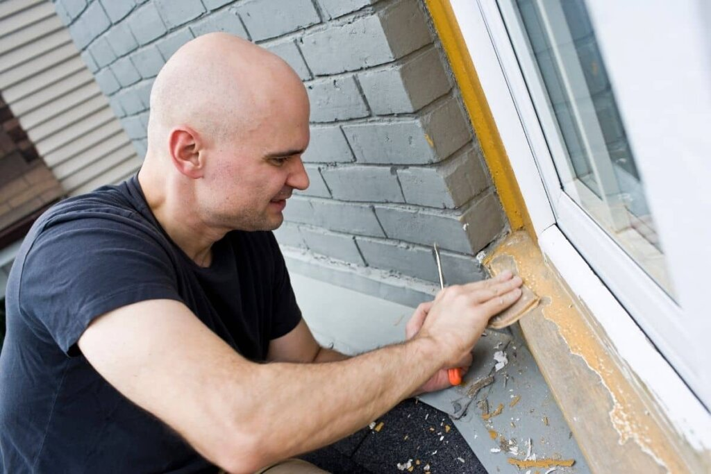 a man sanding a window seal with chipped paint, presumebly to fix it.