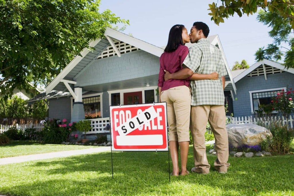 a couple embracing and kissing in front of their house with a sold sign.