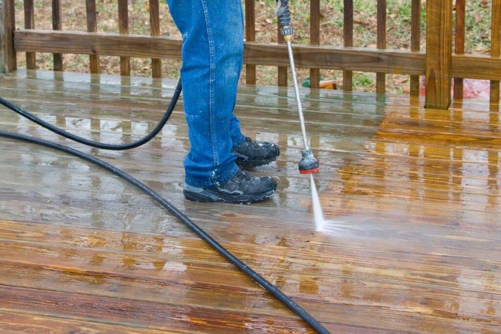 a man pressure washing a wood deck.