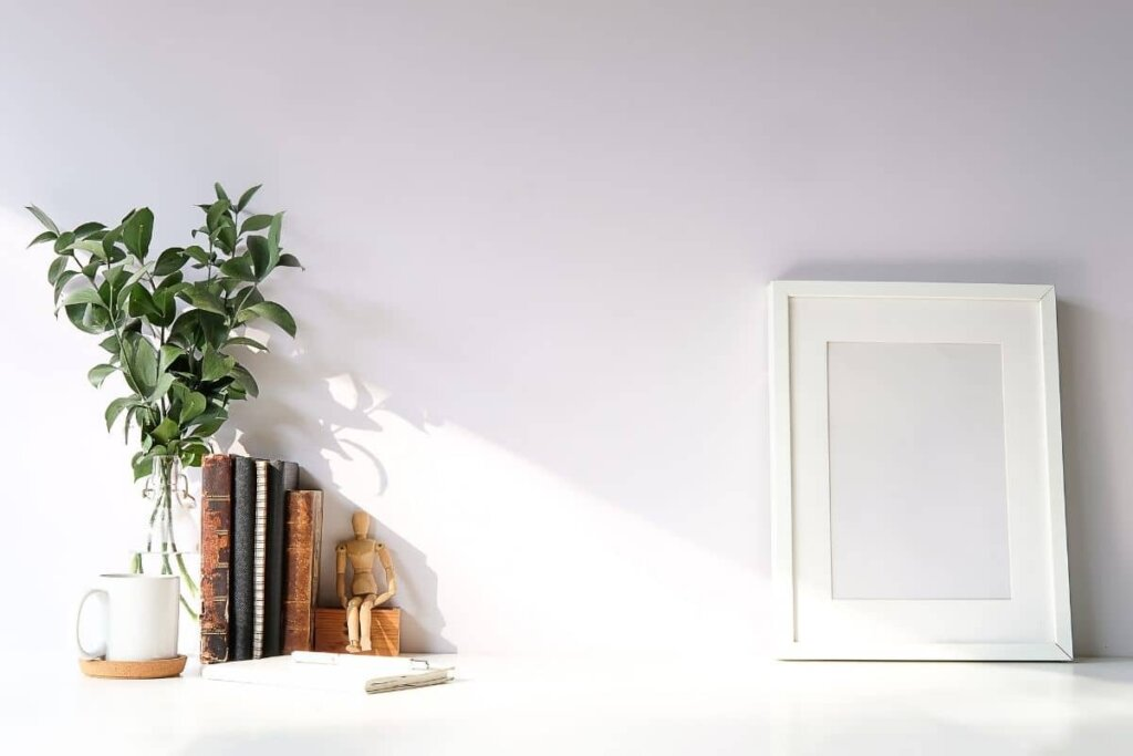 white shelf with a vase of green leaves and old books, a frame with no picture in it