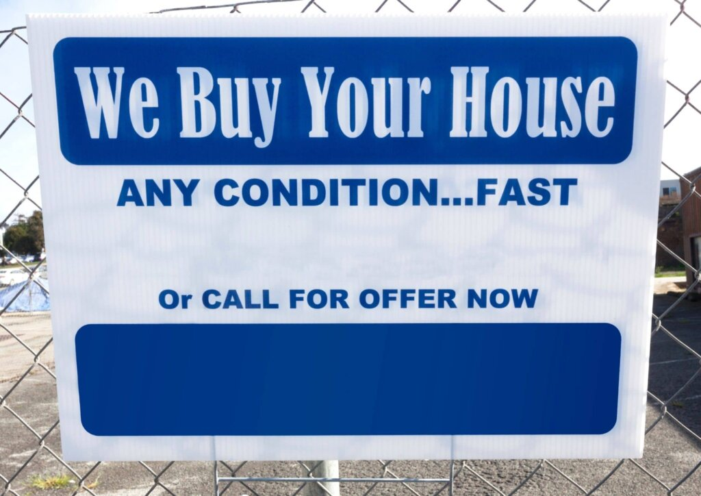 """a white and blue yard sign that says """"we buy your house any condition....fast"""""""