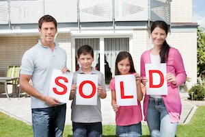 family in Houston holding a sold sign