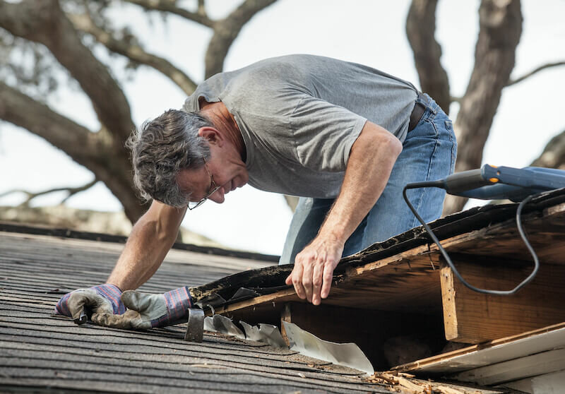 Close up view of man removing rotten wood from leaky roof
