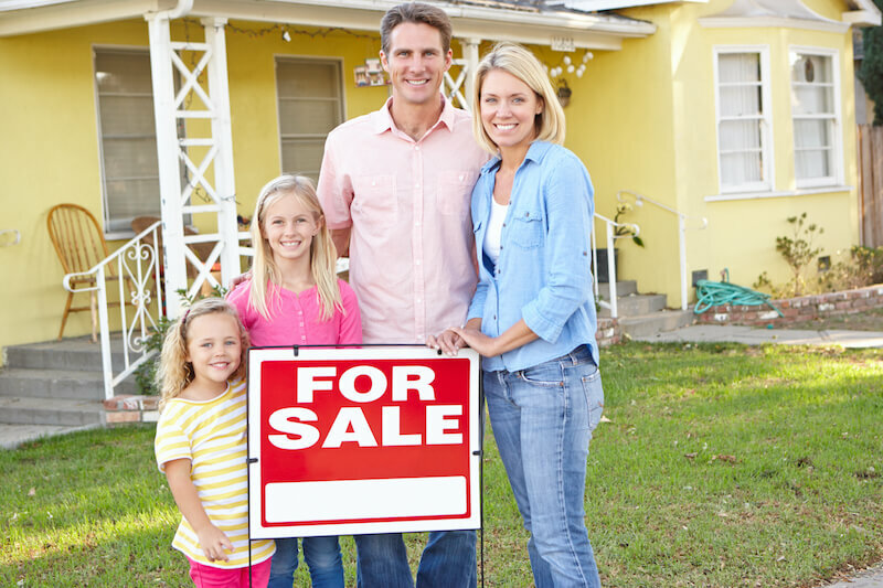 Family Standing By For Sale Sign Outside Home with leaky Roof