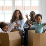 Happy african american parents and kids playing in boxes moving out of Houston