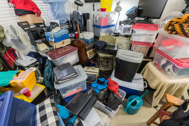 Hoarder room packed with storage boxes, old electronics, files, business equipment and household items