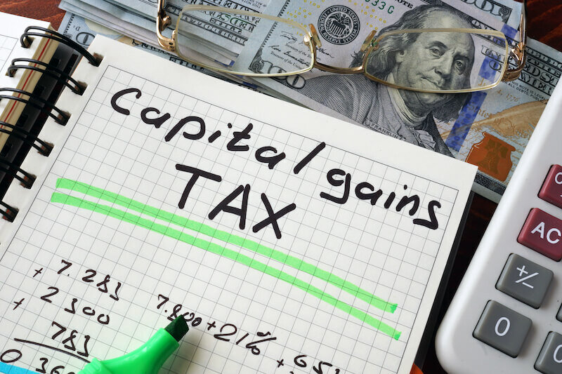 Notebook with capital gains tax sign on a table