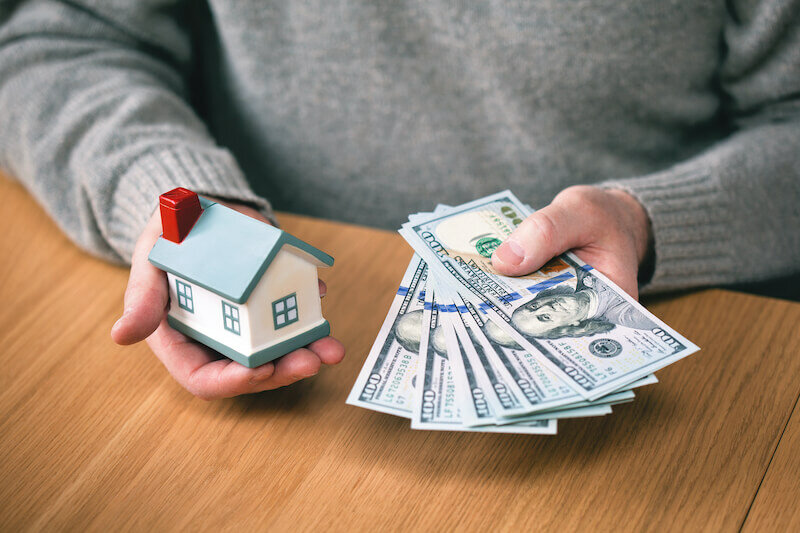 hands holding new hundred-dollar bills and toy house