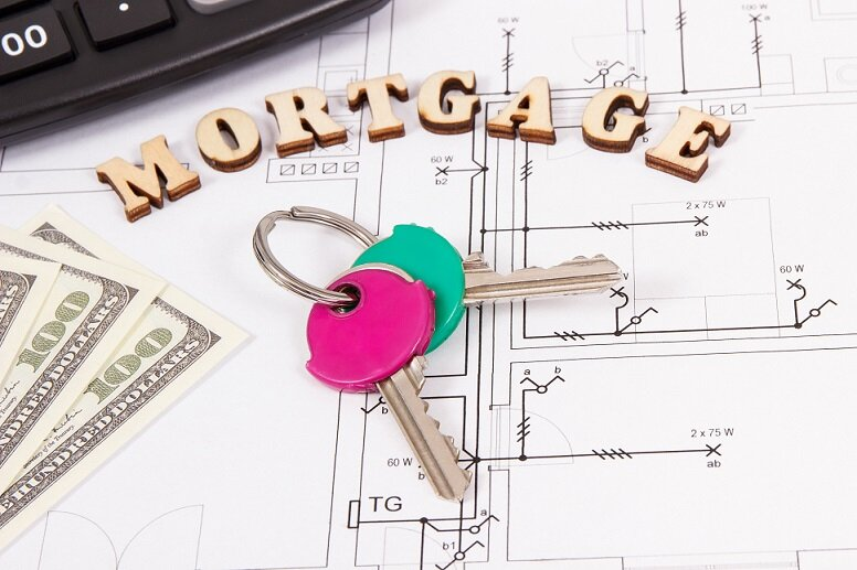 Inscription mortgage, home keys, currencies dollar and calculator on housing plan, calculations of buying or building house concept