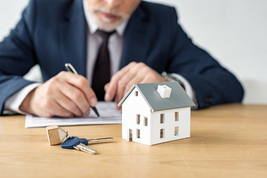 selective focus of house model near keys and house dealer